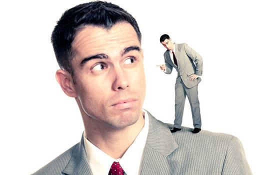 gebrek aan zelfcompassie door een innerlijke criticus op de schouder van een man